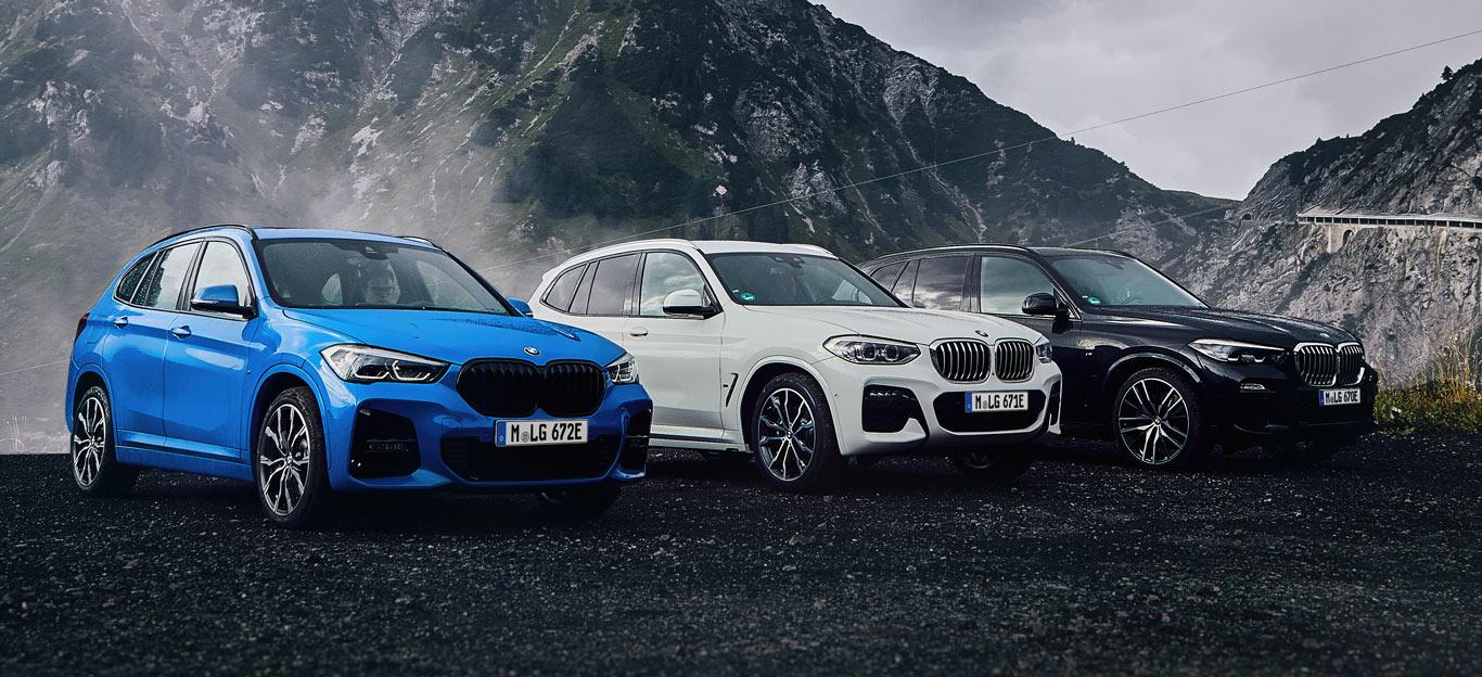 BMW-SUV, drei X-Modelle in Halbseitenansicht von vorne, stehend, blau, weiß und schwarz