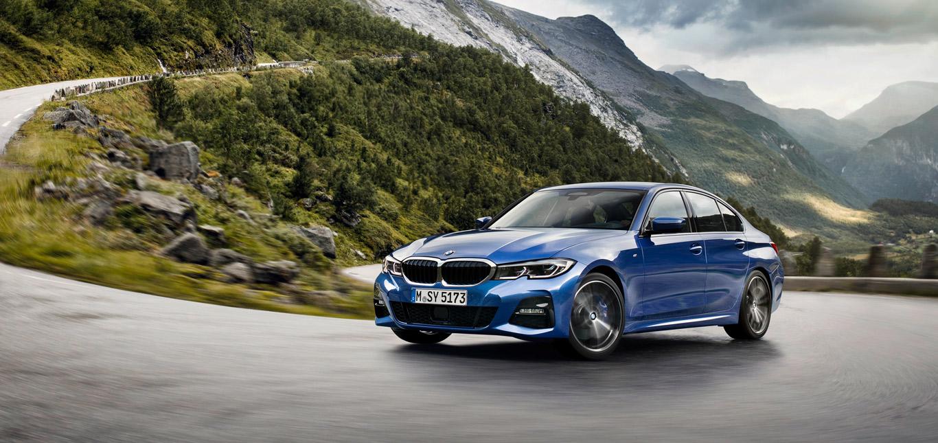 Ein blauer BMW 3, Halbseitenansicht von vorne, fahrend