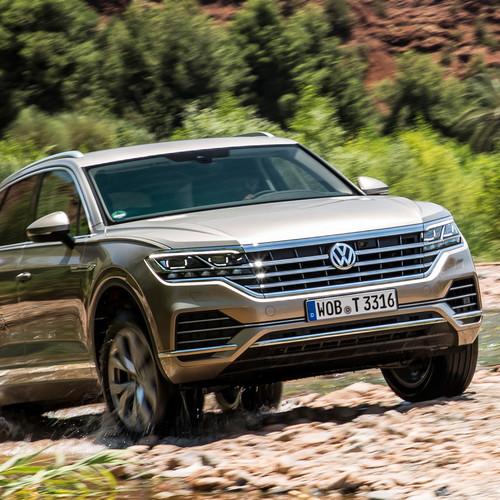 VW Touareg, Halbseitenansicht von vorne, fahrend aus Bachbett, hellbraun