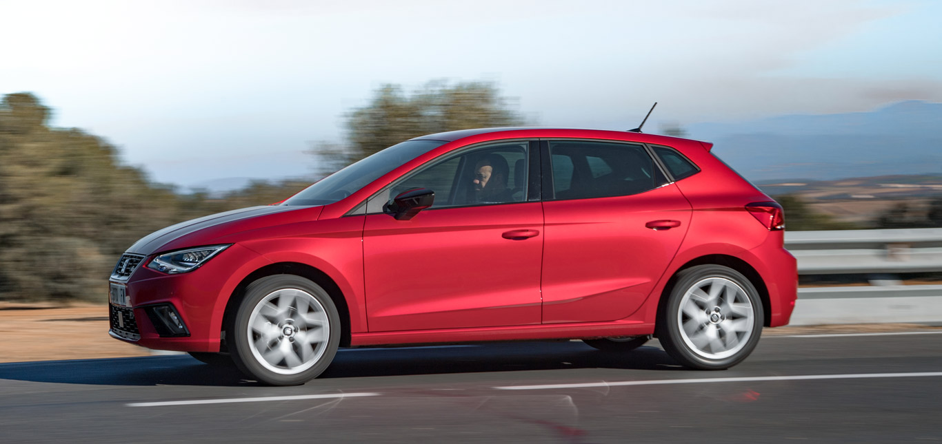 Ein roter Seat Ibiza auf einer Straße, Seitenansicht, fahrend