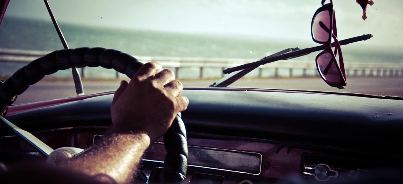 Blick aus einem fahrenden Auto in die Sonne, eine Sonnenbrille hängt am Rückspiegel.
