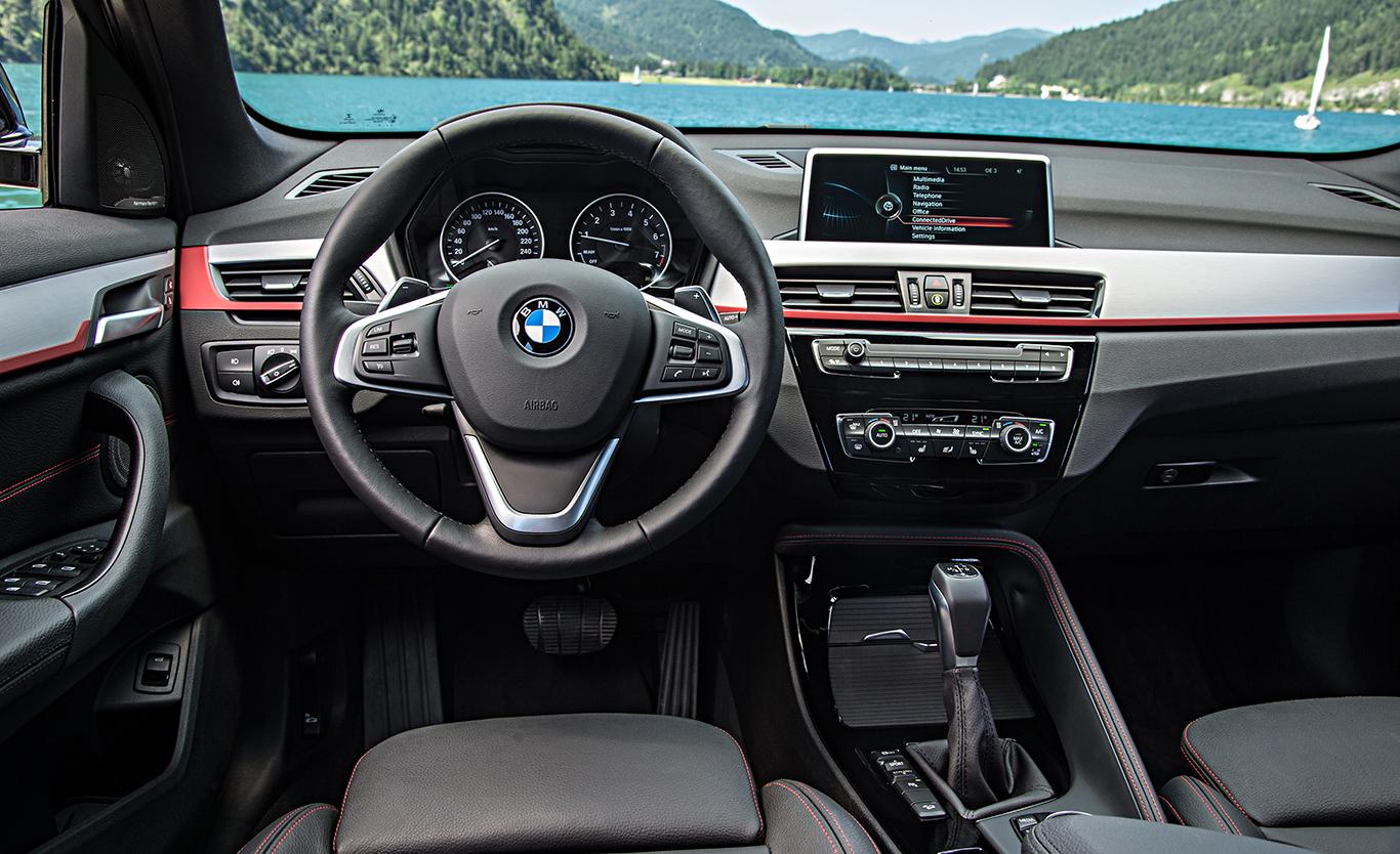 """Typisch für den BMW X1 """"Sport Line"""" ist die markante Hochglanz-Akzentleiste in Korallrot matt."""