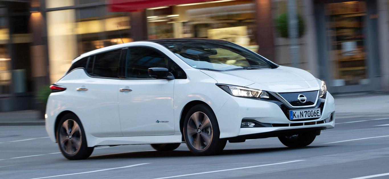 Ein weißer Nissan Leaf, Halbseitenansicht von vorne, fahrend