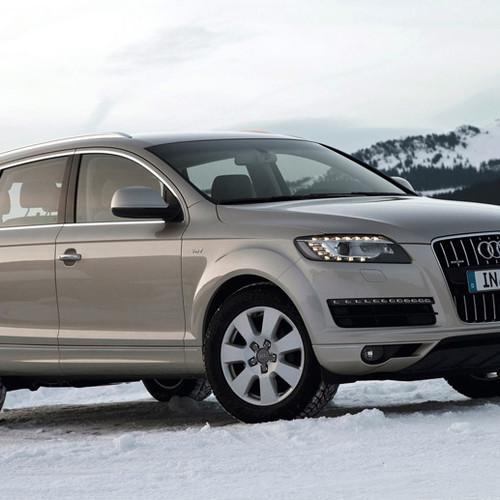 Ein beiger Audi Q7 von der Seite im Schnee