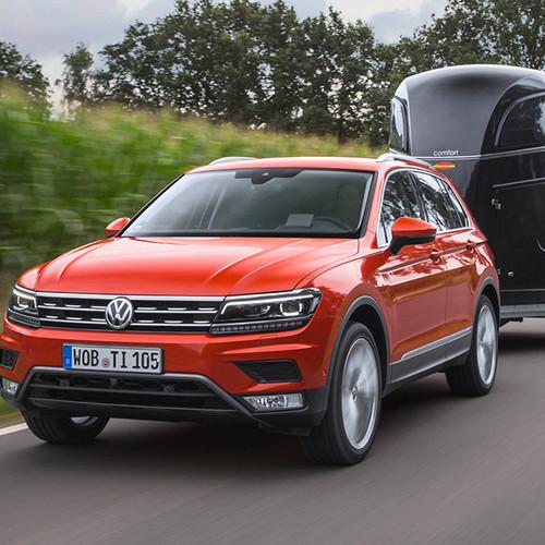 VW Tiguan, Halbseitenansicht von vorn, rot, fahrend mit Anhänger