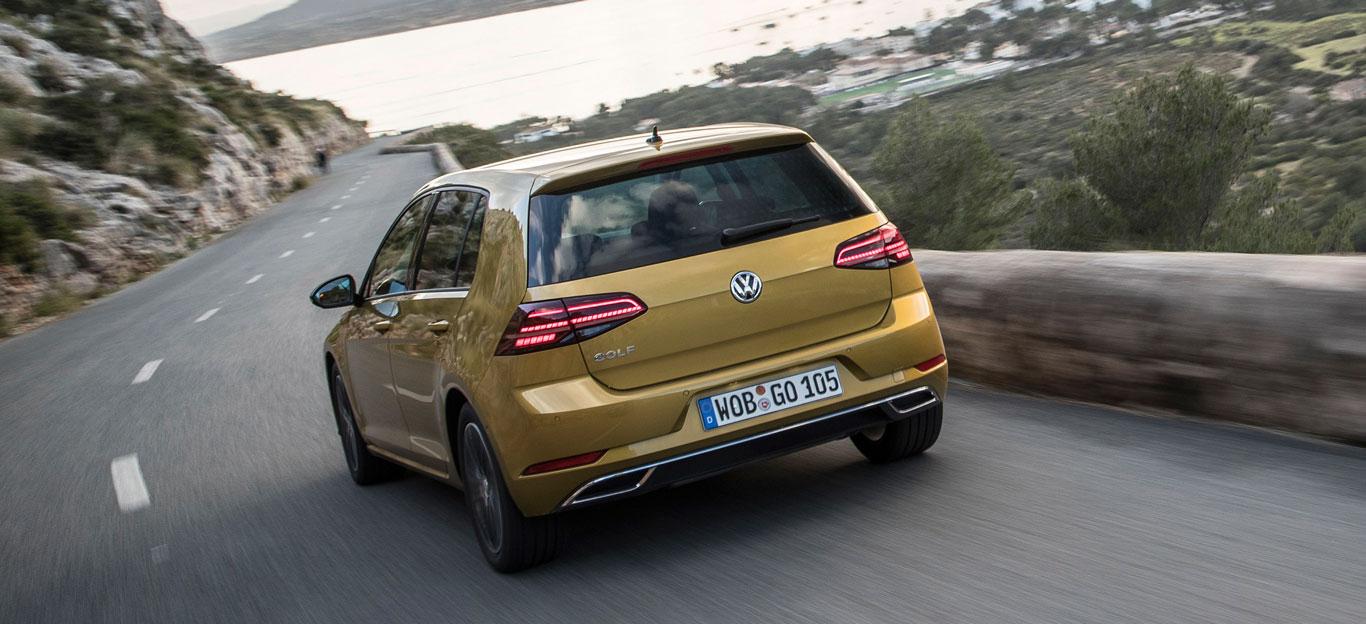 Ein goldener VW Golf auf einer Küstenstraße.