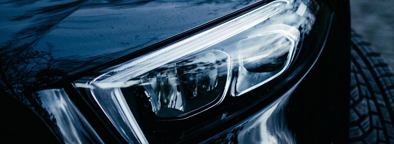 Der Scheinwerfer eines schwarzen Autos.