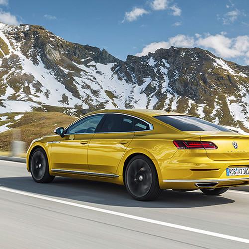 VW Arteon, Halbseitenansicht von hinten, fahrend, kurkumagelb