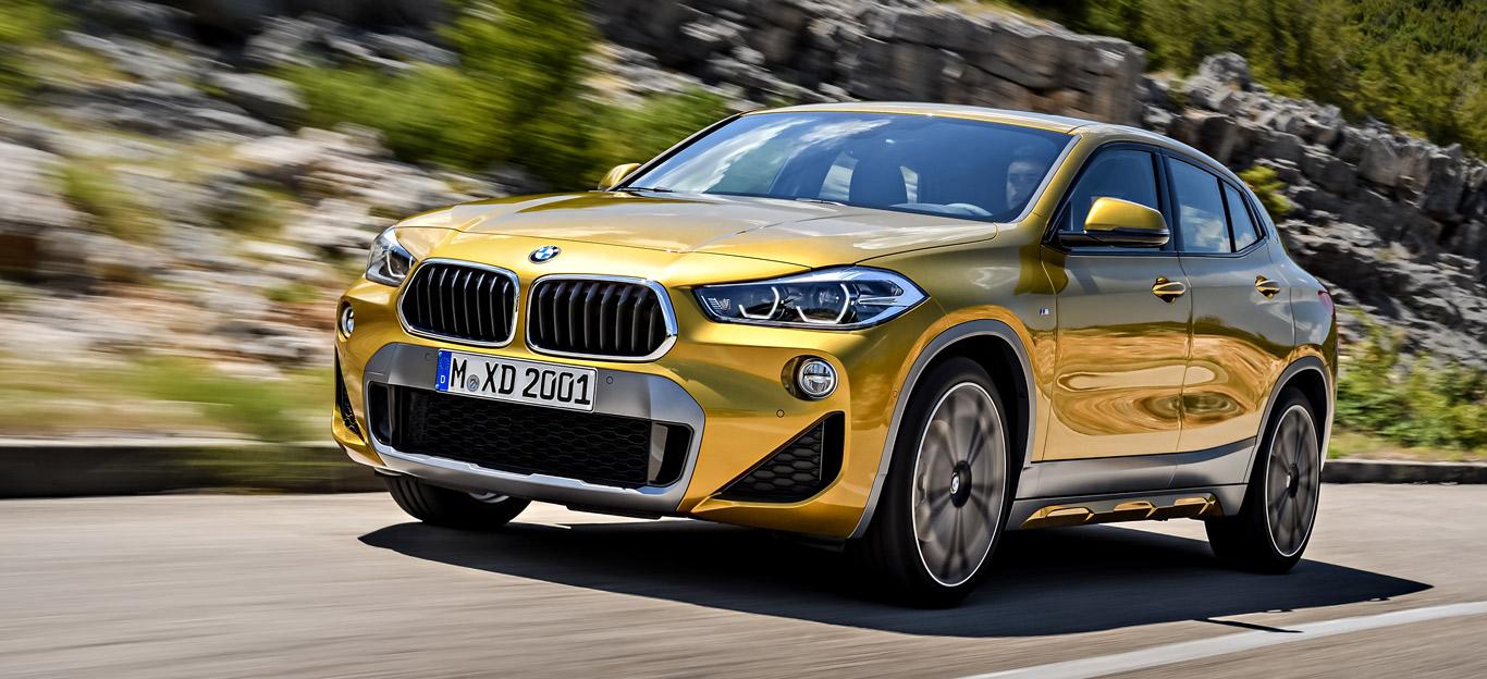 Ein goldener BMW X2 auf einer Landstraße.