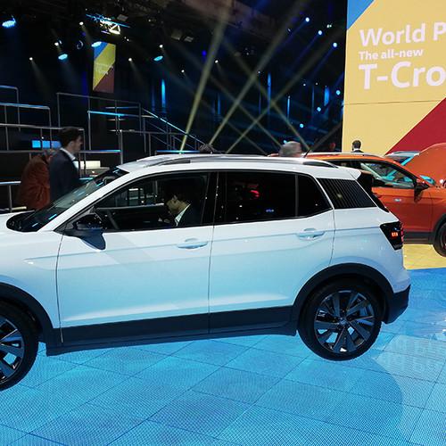 VW T-Cross, zwei Modelle. Im Vordergrund, Seitenansicht, weiß. Im Hintergrund (teilverdeckt): T-Cross, orange