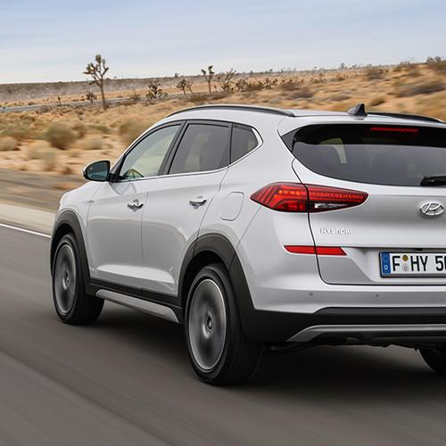 Hyundai Tucson, Halbseitenansicht von hinten, fahrend, hellgrau