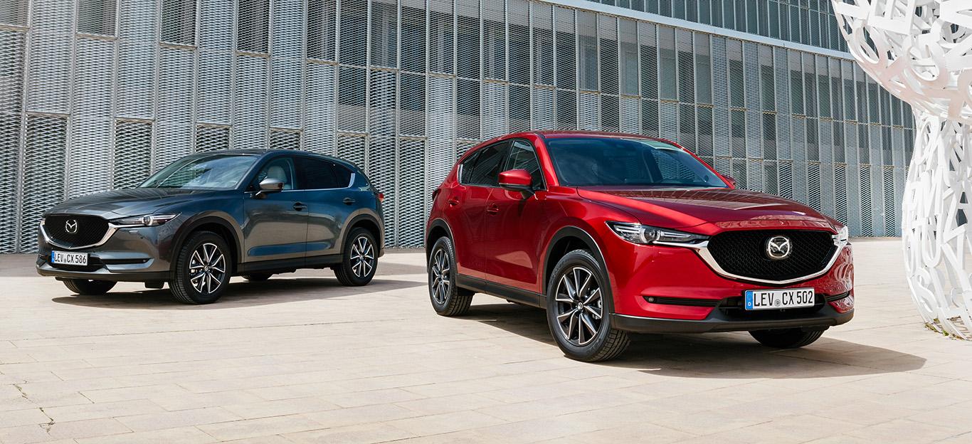 Mazda CX-5, zwei Modelle in Halbseitenansicht von vorne, stehend, grau und rot