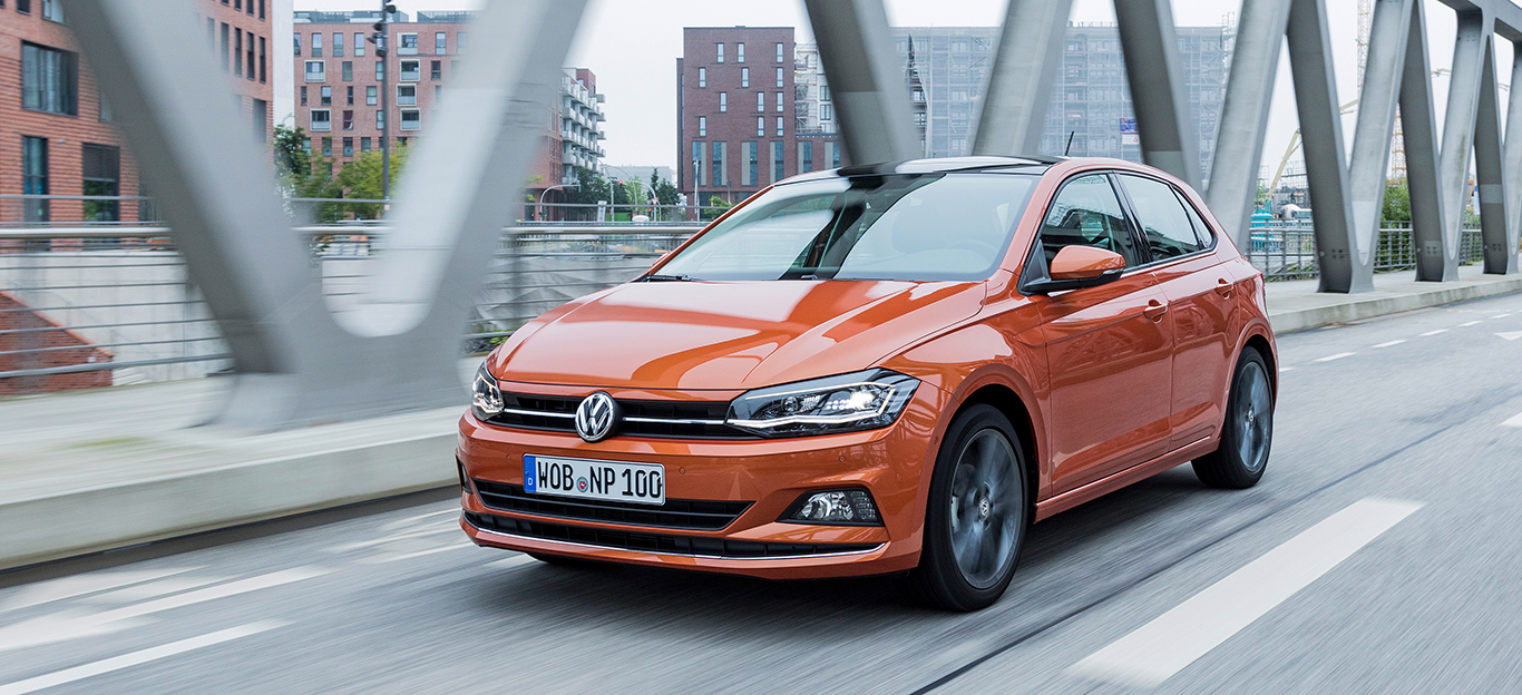 VW Polo, Halbseitenansicht von vorn, fahrend, orange