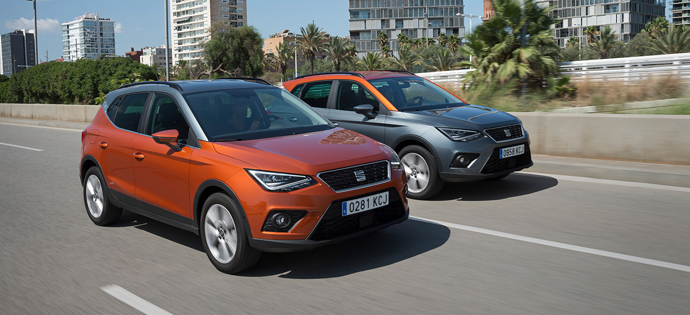 Seat Arona, zwei Modelle in Halbseitenansicht von vorne, fahrend, orange und silbergrau