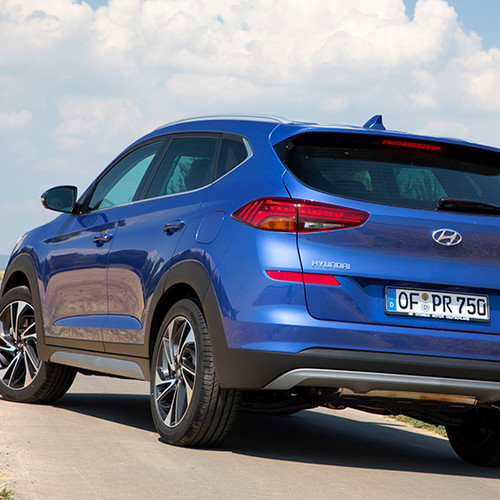 Hyundai Tucson, Halbseitenansicht von hinten, fahrend, blau