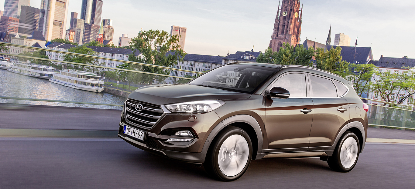 Hyundai Tucson braun in Frankfurt fahrend Seitenansicht