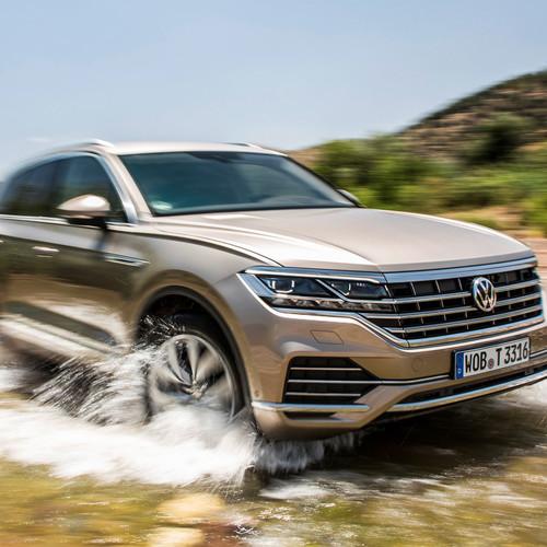 VW Touareg, Halbseitenansicht von vorne, fahrend durch Bachbett, hellbraun