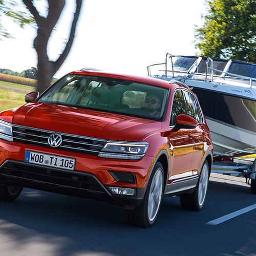 VW Tiguan, Halbseitenansicht von vorn mit Boot-Anhänger, fahrend, orange